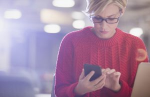 Businesswoman working late at laptop, texting with cell phone in dark office